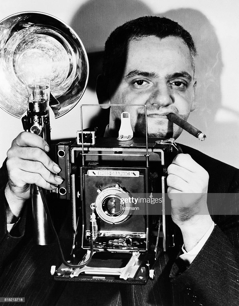 Arthur Fellig, known as '<a gi-track='captionPersonalityLinkClicked' href=/galleries/search?phrase=Weegee&family=editorial&specificpeople=207086 ng-click='$event.stopPropagation()'>Weegee</a>,' chomps his cigar and holds his Speed Graphic camera. A photographer of New York crime, disasters, and urban squalor, he got his nickname from the fortunetelling game of Ouija, for his uncanny ability to be the first at the scene.