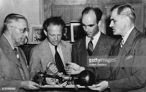 Arthur H Compton the American physicist discusses the cosmic ray meter with fellow physicists at a meeting of Nobel Prize winners at the University...