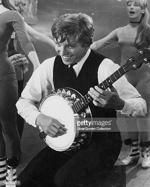 Arthur Kipps played by English rock 'n' roll singer and actor Tommy Steele playing a banjo in 'Half a Sixpence' directed by George Sidney 1967