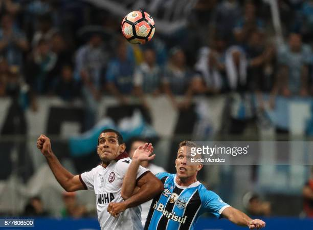 Arthur of Gremio struggles for the ball with Jose Sand of Lanus during a first leg match between Gremio and Lanus as part of Copa Bridgestone...