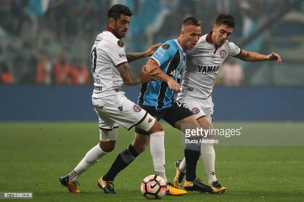 Arthur of Gremio struggles for the ball with Roman Martinez and Alejandro Silva Gonzalez of Lanus during a first leg match between Gremio and Lanus...