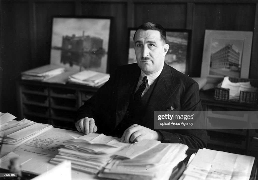 Arthur Rank (1888 - 1972), the head of the Rank cinema company seated in his London office.