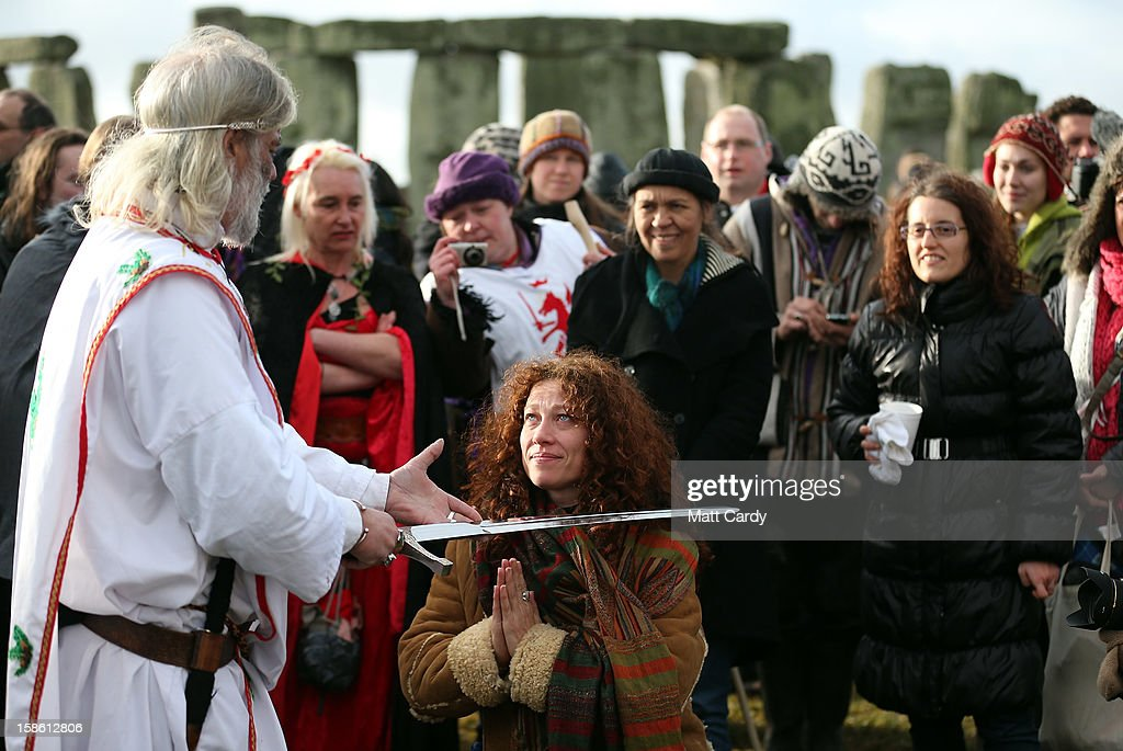 Arthur Uther Pendragon (L) knights a woman as Druids conduct a ceremony following the traditional winter solstice celebrations at Stonehenge to coincide with the supposed Mayan Apocalypse, on December 21, 2012 in Wiltshire, England. Predictions that the world will end today as it marks the end of a 5,125-year-long cycle in the ancient Maya calendar, encouraged a larger than normal crowd to gather at the famous historic stone circle to celebrate the sunrise closest to the Winter Solstice, the shortest day of the year.
