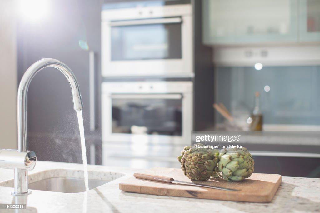 Artichokes on cutting board in modern domestic kitchen : Stock Photo
