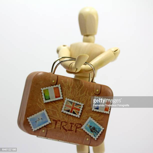 Articulated doll carrying a heavy suitcase