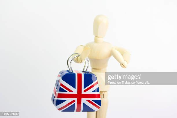 Articulated doll carrying a heavy suitcase with the English flag