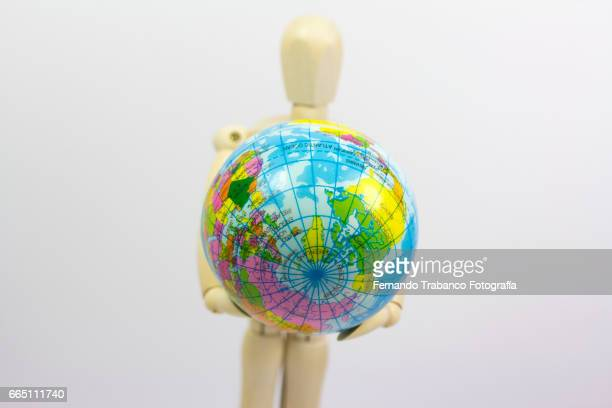 Articulated doll holding a globe. Travel agent and vacation
