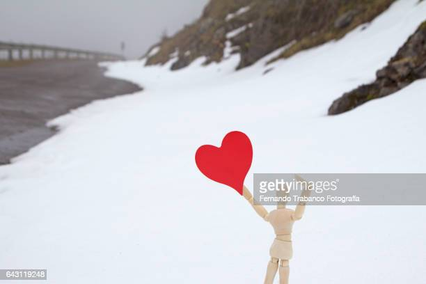 Articulated doll with a red heart in Landscape of mountains and snowy roads