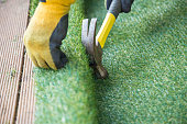 Artificial grass, turf installation alongside decking. A hammer in being used to nail the turf into place. A yellow work glove can be seen.
