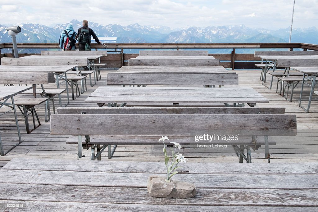 Artificial edelweiss stand on the tables of restaurants terrace at the peak 'Nebelhorn' while a pair looks to the 'Allgaeu Alps'