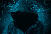 Unrecognizable hooded hacker hacking artificial neural network. Cybersecurity concept.