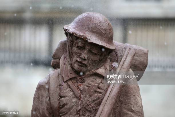 TOPSHOT Artificial rain falls on the 'Mud Soldier' statue which is sculpted from sand and mud from Passchendaele during the unveiling ceremony on the...