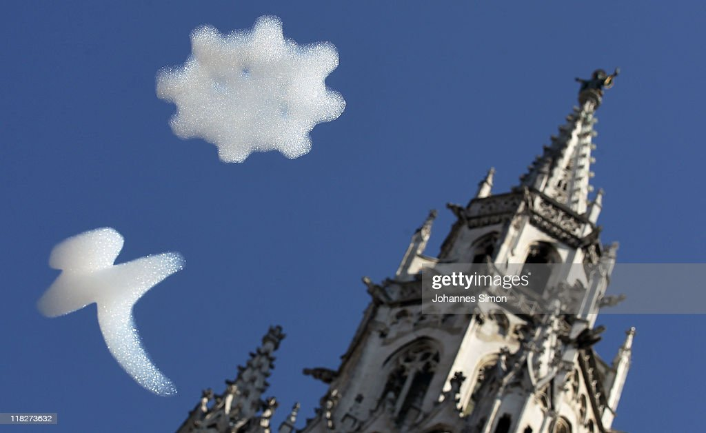 Artificial snowflakes hover around the townhall clocktower at Marienplatz square during the public viewing for the IOC decision on 2018 olympic winter games on July 6, 2011 in Munich, Germany.