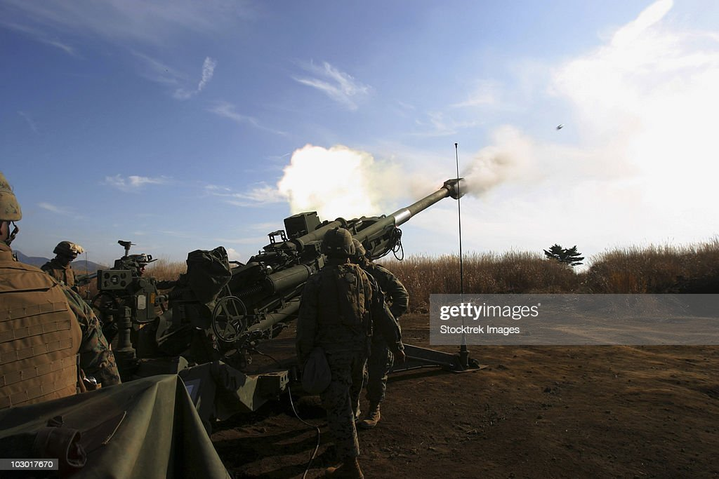 Artillerymen fire a 155mm round out of an M777 lightweight howitzer.