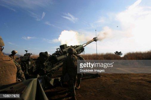 Artillerymen fire a 155mm round out of an M777 lightweight howitzer.