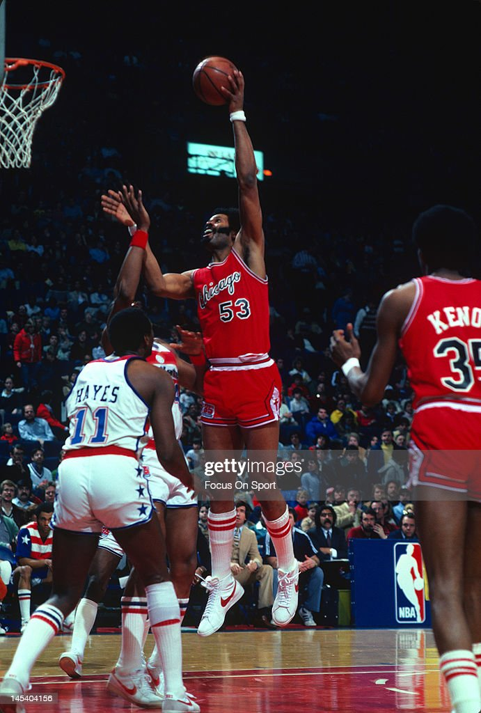 Artis Gilmore of the Chicago Bulls goes up to shoot over Rick Mahorn and Elvin Hayes of the Washington Bullets during an NBA basketball game circa...