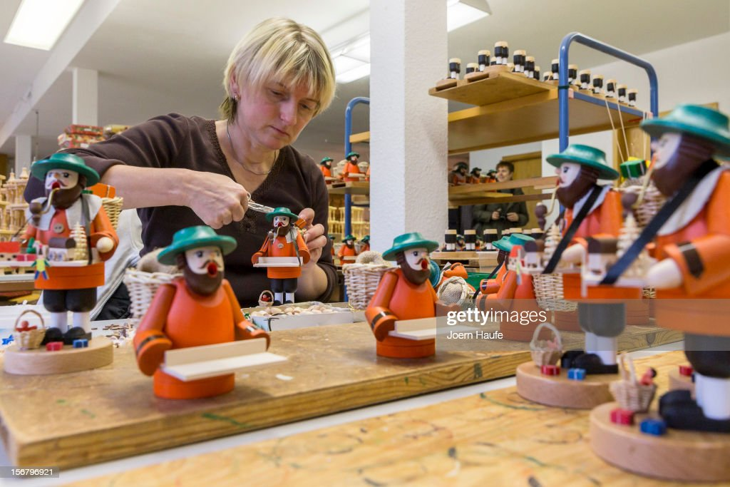 Artisan Annett Weber glues together the wooden parts for a Smoking Man decoration at the Richard Glaesser GmbH wooden toy manufactory on November 20, 2012 in Seiffen, Germany. Located in the Ore Mountains, Seiffen is home to a plethora of workshops that specialize in hand-painted wooden Christmas decorations in a tradition going back centuries.