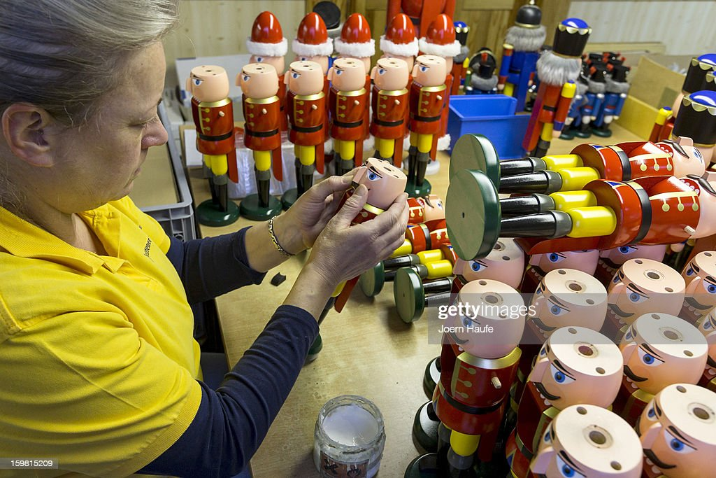 Artisan Christina Reimer at the Seiffener Volkskunst Christmas decorations manufactory assembles a nutcracker on November 20, 2012 in Seiffen, Germany. Located in the Ore Mountains, Seiffen is home to a plethora of workshops that specialize in hand-painted wooden Christmas decorations in a tradition going back centuries.