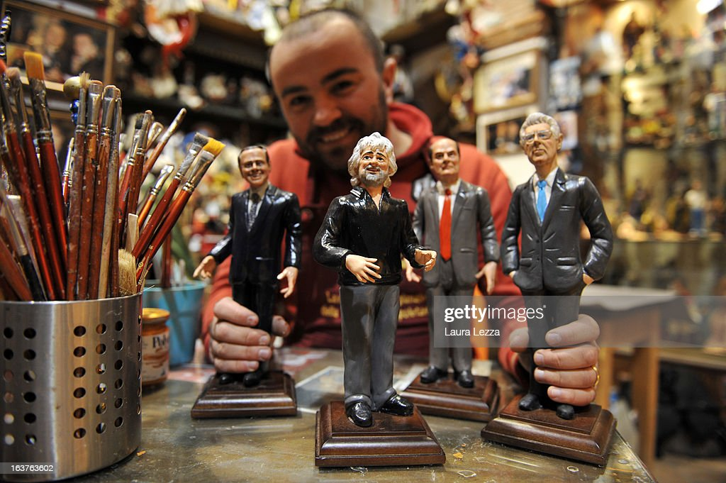 Artisan Genny Di Virgilio poses for a photo with some of his commemorative figurine depicting italian politicians (R to L) Mario Monti, Pierluigi Bersani, Beppe Grillo and Silvio Berlusconi are displayed at San Gregorio Armeno on March 14, 2013 in Naples, Italy. Members of the new Italian parliament are in talks to negotiate the formation of a coalition government. If they fail to reach an agreement another election will be held.