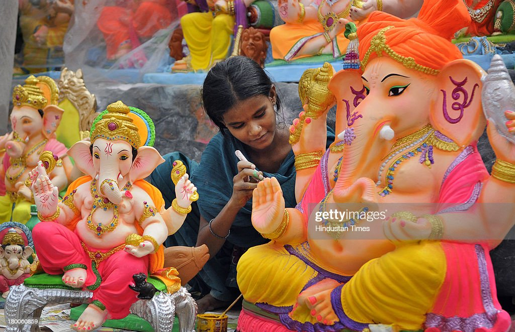 Artisan giving final touch to idols of Lord Ganesha on the eve of Hindu festival Ganesha Chaturthi on September 8, 2013 in New Delhi, India. Ganesh Chaturthi, which begins from September 9, is celebrated as the birthday of Lord Ganesha who is widely worshiped by Hindus as the god of wisdom, prosperity and good fortune.