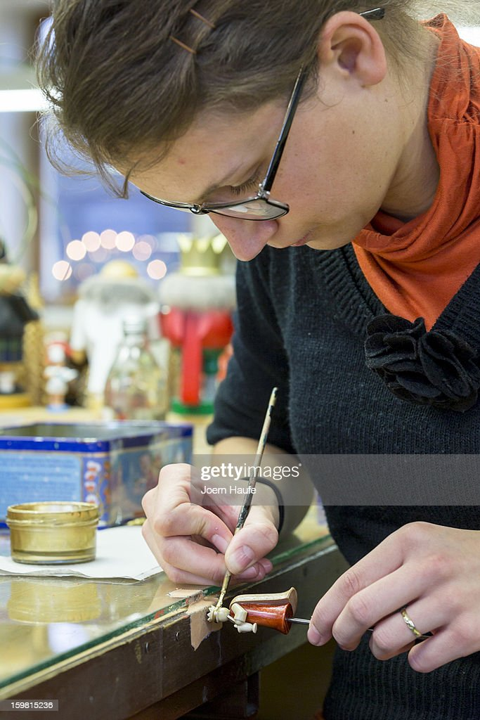Artisan Mirjam Boehme paints wooden figurines at the Richard Glaesser GmbH wooden toy manufactory on November 20, 2012 in Seiffen, Germany. Located in the Ore Mountains, Seiffen is home to a plethora of workshops that specialize in hand-painted wooden Christmas decorations in a tradition going back centuries.