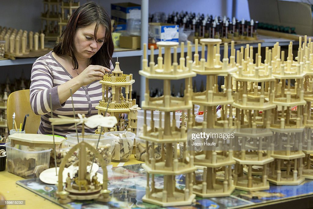 Artisan Silke Koenig glues together wooden Christmas pyramids at the Richard Glaesser GmbH wooden toy manufactory on November 20, 2012 in Seiffen, Germany. Located in the Ore Mountains, Seiffen is home to a plethora of workshops that specialize in hand-painted wooden Christmas decorations in a tradition going back centuries.