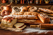 Artisanal bakery: Group of fresh mixed breads and rolls. Artisanal bakery is bread made by a craftsperson using mainly traditional techniques. Also, it is usually made by hand, however, many artisanal