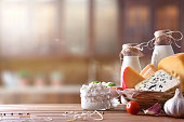 Assortment of artisanal dairy products on a wooden table in rustic kitchen. Front view. Horizontal composition