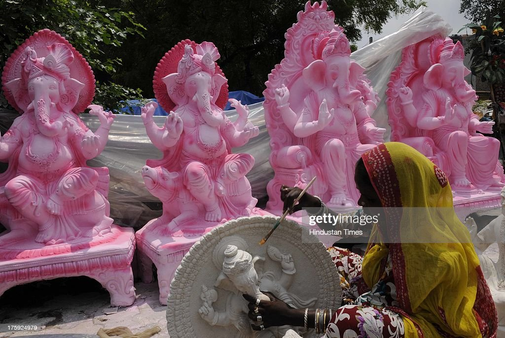 Artisans paint idols of the Hindu Lord Ganesha on a roadside at NH 24 on August 10, 2013 in New Delhi, India. The idols are being prepared for the popular twelve-day Hindu religious festival 'Ganesh Chaturthi' festival, which will be celebrated from the first week of September.