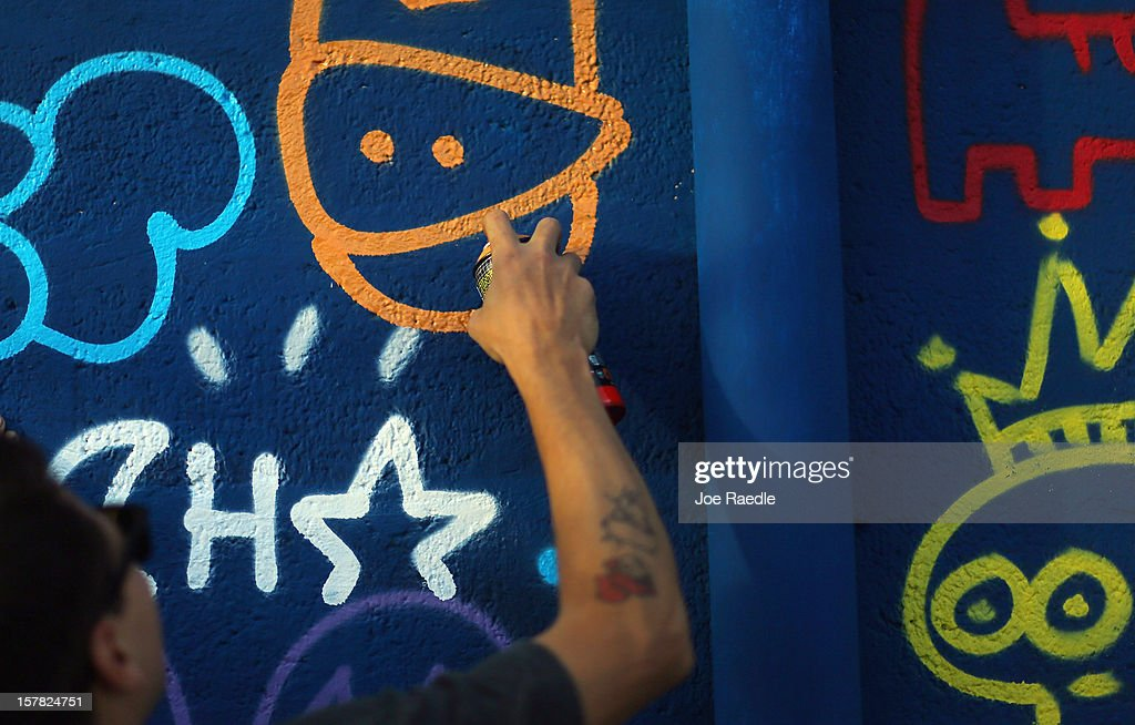 Artist, Alberto Vejarano, works on his painting on the wall of a building as he participates in the Wynwood Walls art project on December 6, 2012 in Miami, Florida. The art project along with many other satellite shows around the city coincide with the International art show, 'Art Basel', which runs until the 9th of December.