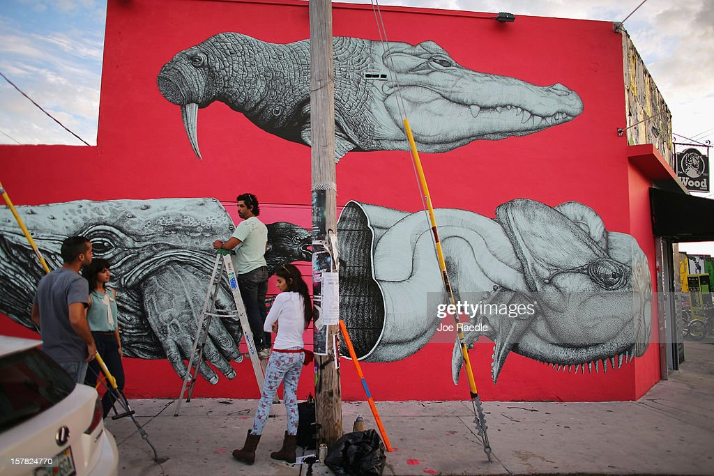 Artist, Alexis Diaz, stands on a ladder as he works on his painting on the wall of a building as he participates in the Wynwood Walls art project on December 6, 2012 in Miami, Florida. The art project along with many other satellite shows around the city coincide with the International art show, 'Art Basel', which runs until the 9th of December.