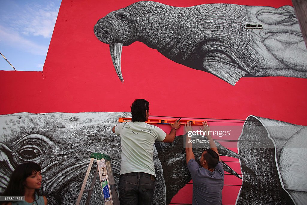 Artist, Alexis Diaz (L) with the help of his friend, Fernando Romero, work on his painting on the wall of a building as he participates in the Wynwood Walls art project on December 6, 2012 in Miami, Florida. The art project along with many other satellite shows around the city coincide with the International art show, 'Art Basel', which runs until the 9th of December.