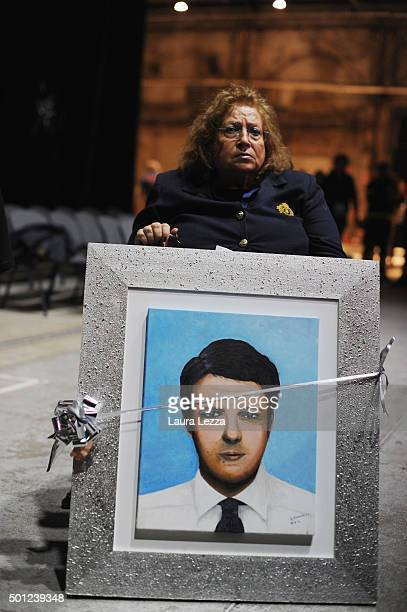 Artist and supporter of Italian Prime Minister Matteo Renzi Maria Giovanna Di Raimondo with a portrait of Prime Minister as a gift during the meeting...