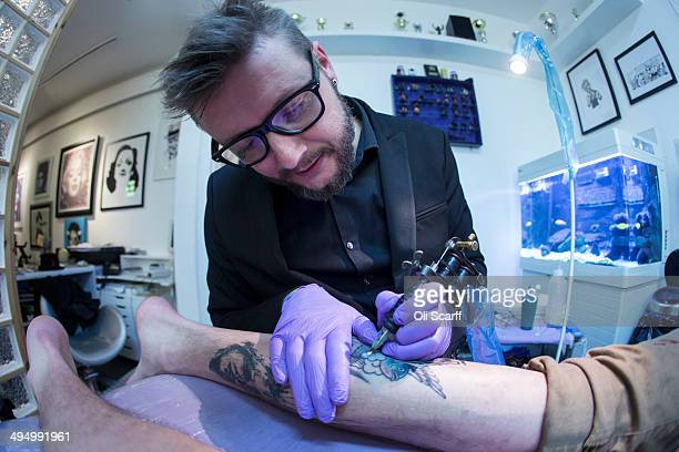 Artist and tattooist Dan Gold creates a tattoo featuring an image of Albert Einstein in his West Hampstead studio on April 22 2014 in London England...