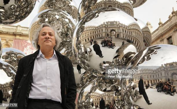Artist Anish Kapoor stands with his new sculpture entitled 'Tall Tree and the Eye' in the courtyard of The Royal Academy on September 22 2009 in...
