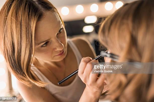 Artist applying make-up on fashion model