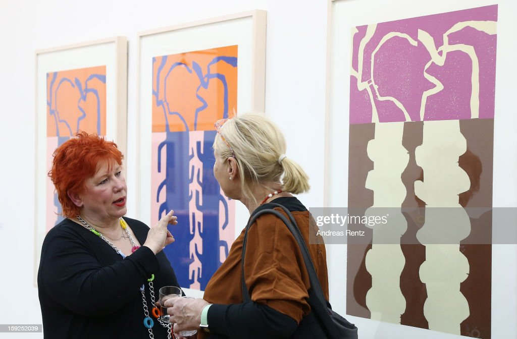 Artist Barbara Salesch (L) talks to a guest next to her art work (title: 'Farbserie 1 - 7teilig') at ROOT gallery on January 10, 2013 in Berlin, Germany. The exhibition will open January 10 and run through February 3.