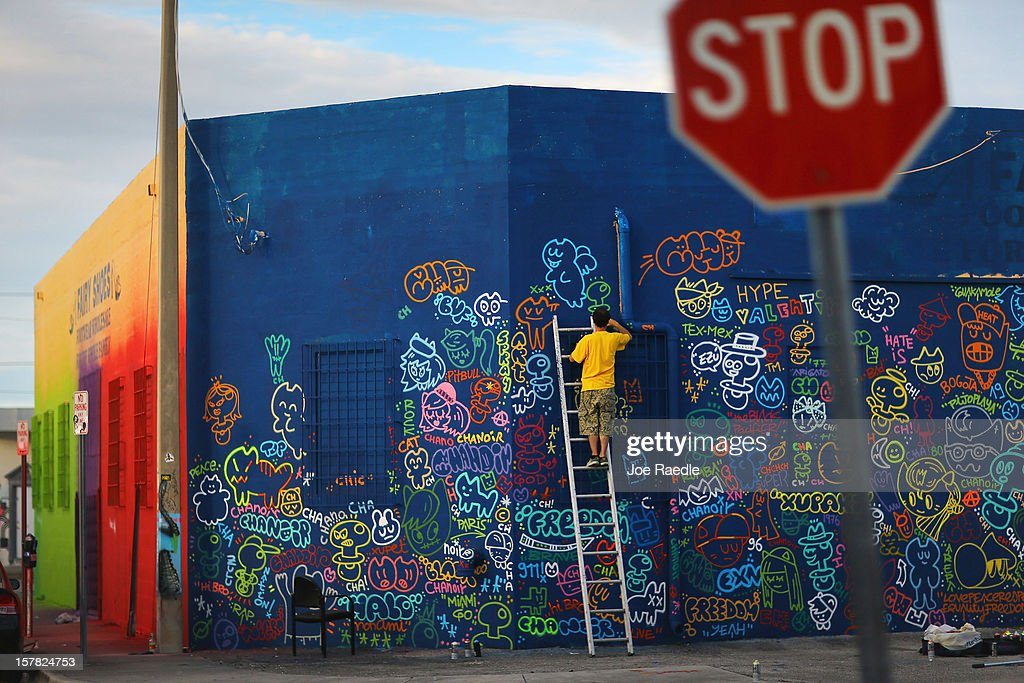 Artist, Carlos Black Pacifier, works on his painting on the wall of a building as he participates in the Wynwood Walls art project on December 6, 2012 in Miami, Florida. The art project along with many other satellite shows around the city coincide with the International art show, 'Art Basel', which runs until the 9th of December.