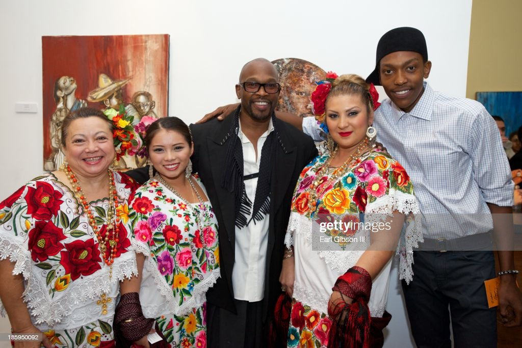 Artist Chaz Guest and his son Zuhri Guest pose with traditional dancers at the 'Visions Of Mexico' International Retrospective at Quinn Studios on October 25, 2013 in Santa Monica, California.