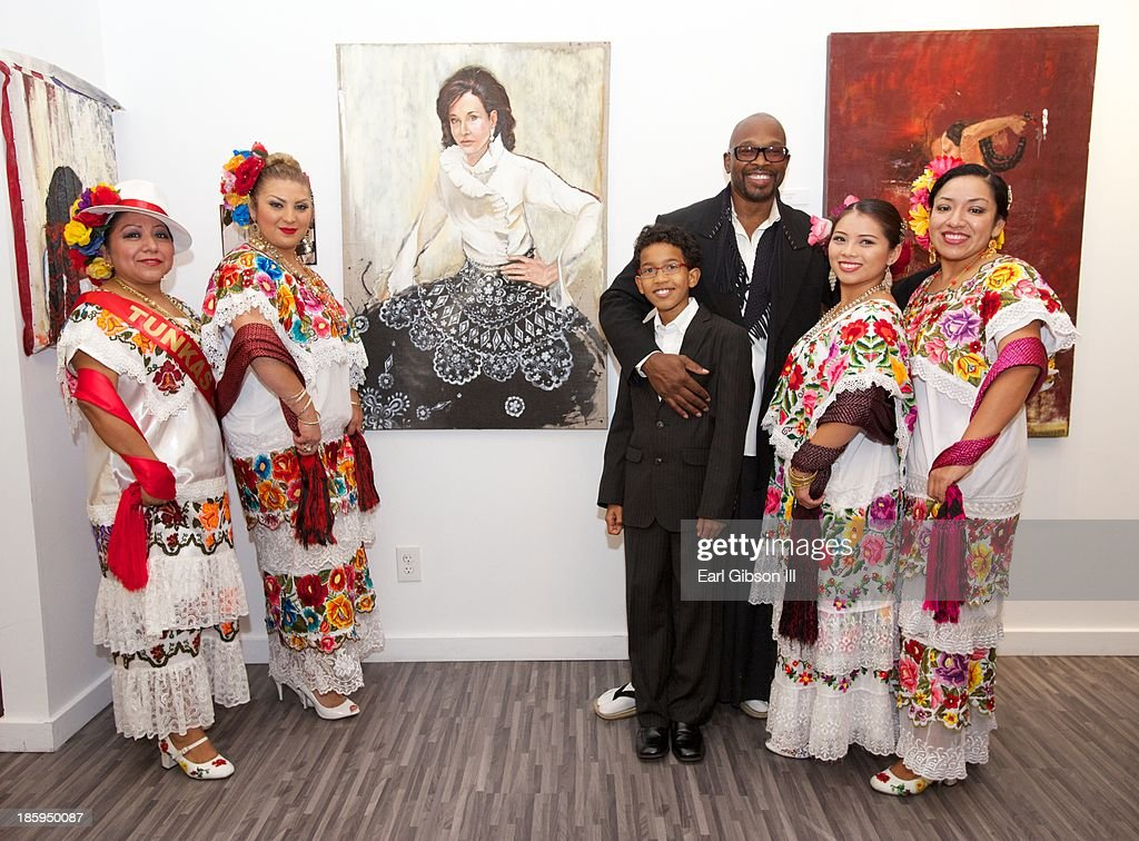 Artist Chaz Guest (rear) poses with his son Xian Wong-Guest and traditional mexican dancers along with some of his retrospective paintings at Quinn Studios on October 25, 2013 in Santa Monica, California.