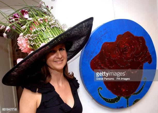 Artist Cindy Lass displays a piece of artwork which is signed by David and Victoria Beckham featuring a flower adorned with Swarovski crystals at the...