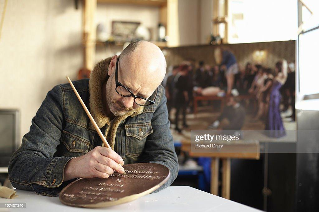 Artist cleaning bronze plaque artwork : Stock Photo