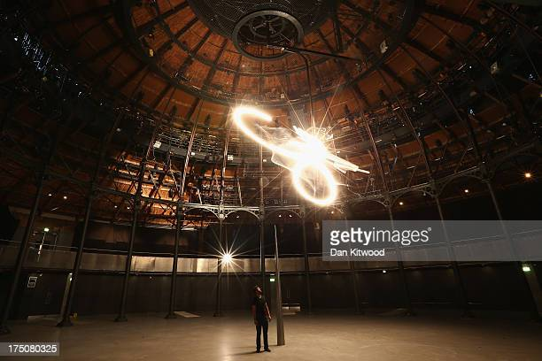 Artist Conrad Shawcross stands under his installation called 'Timepiece' at The Roundhouse on July 31 2013 in London England The largescale light...