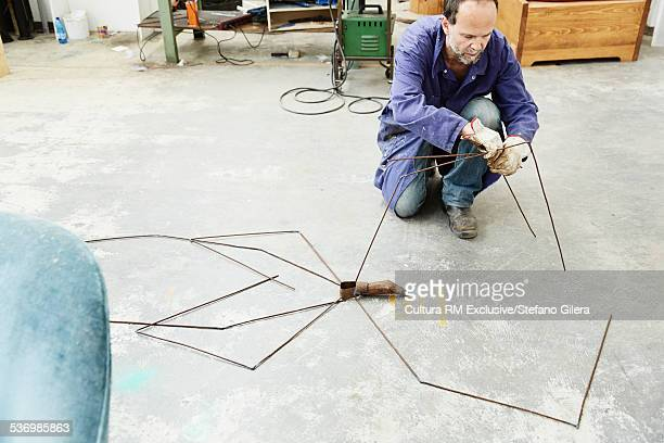 Artist constructing artwork from metal