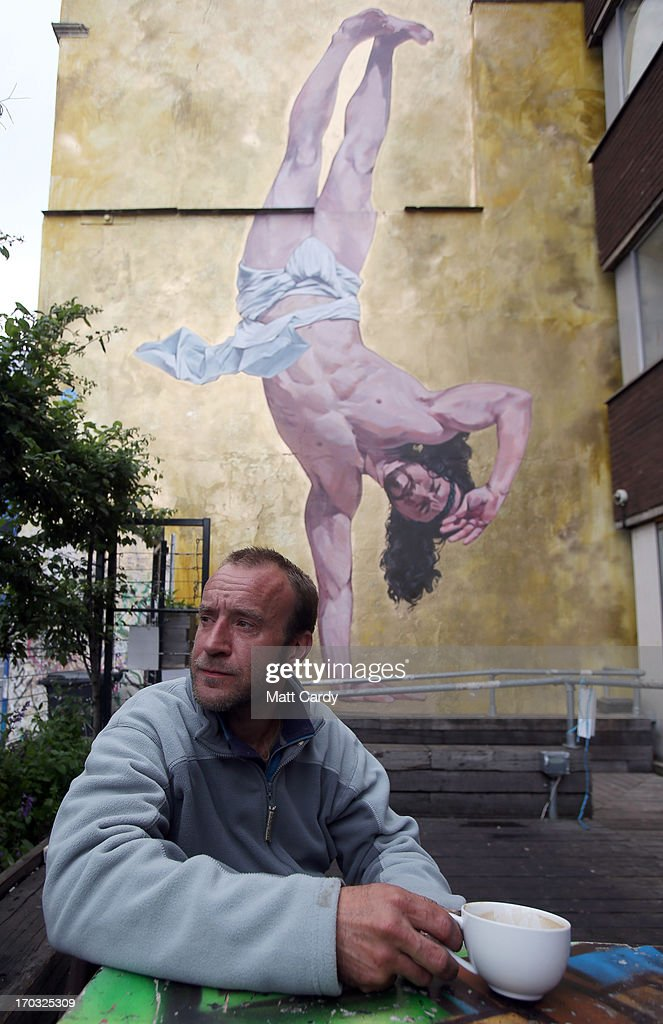 Artist Cosmo Sarson sits besides a giant mural of Jesus breakdancing that he has painted on the 8.5 metre wall beside The Canteen in Stokes Croft and is being officially unveiled this evening, on June 11, 2012 in Bristol, England. The artist was commissioned by The Canteen to paint the wall, which is directly opposite Banksy's Mild Mild West. The controversial 'Breakdancing Jesus', which took 4 days to paint and involved a kilo of glitter and was inspired by an actual event in the Vatican where breakdancers performed to an applauding Pope John Paul II in 2004, is likely to be the latest attraction for graffiti tourists visiting Bristol, often seen the spiritual home of underground artist Banksy.