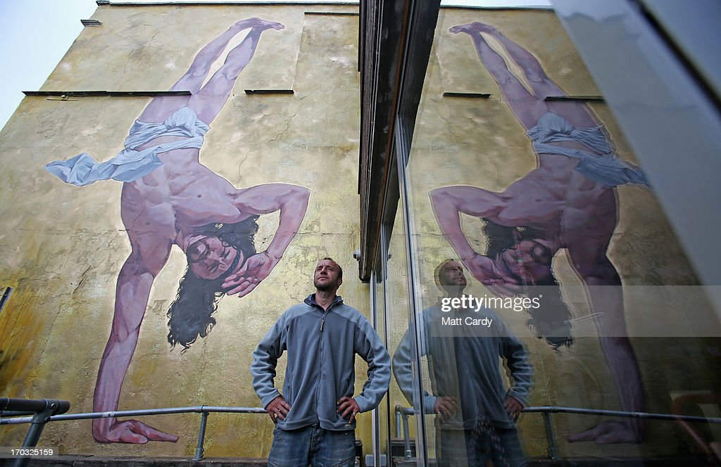 Artist Cosmo Sarson stands besides a giant mural of Jesus breakdancing that he has painted on the 8.5 metre wall beside The Canteen in Stokes Croft and is being officially unveiled this evening, on June 11, 2012 in Bristol, England. The artist was commissioned by The Canteen to paint the wall, which is directly opposite Banksy's Mild Mild West. The controversial 'Breakdancing Jesus', which took 4 days to paint and involved a kilo of glitter and was inspired by an actual event in the Vatican where breakdancers performed to an applauding Pope John Paul II in 2004, is likely to be the latest attraction for graffiti tourists visiting Bristol, often seen the spiritual home of underground artist Banksy.