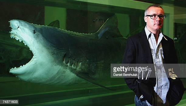 Artist Damien Hirst poses for photographs in front of his piece named 'Death Explained' a disected shark suspended in 2 separate containers in...