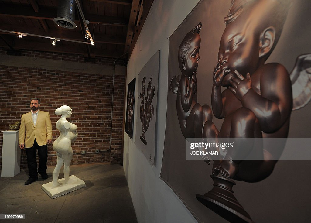 Artist Daniel Edward presents his new sculpture of pregnant celebrity Kim Kardashian, with the belly fully accessible for visitors to rub for 'good luck,' at LAB ART Gallery in Hollywood, California, on June 5, 2013. The statue is part of Edward's ''Celebrity Baby Boomer'' series. AFP PHOTO/JOE KLAMAR 'MANDATORY MENTION OF THE ARTIST UPON PUBLICATION'