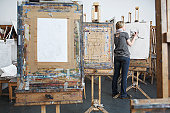 Artist drawing charcoal portrait among easels in studio, back view
