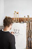 Artist drawing charcoal portrait in studio, back view